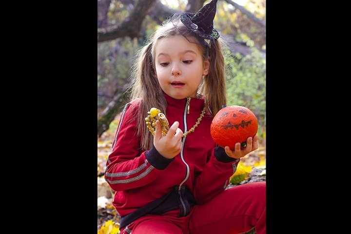 Girl in a witchs halloween hat and pumpkins in forest.