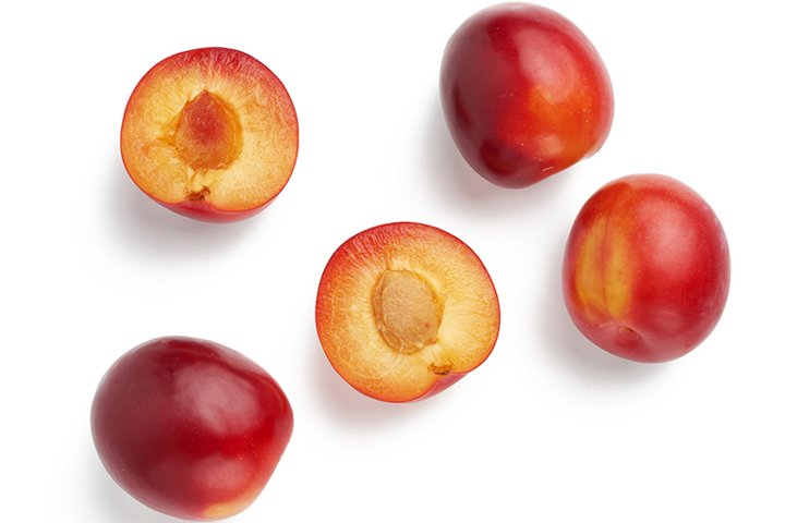 ripe red whole and halves of plum
