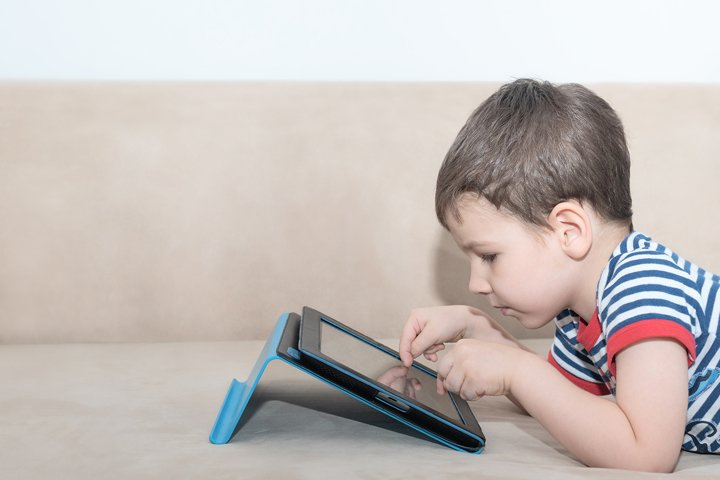 Toddler boy is lying on the sofa with a tablet studying