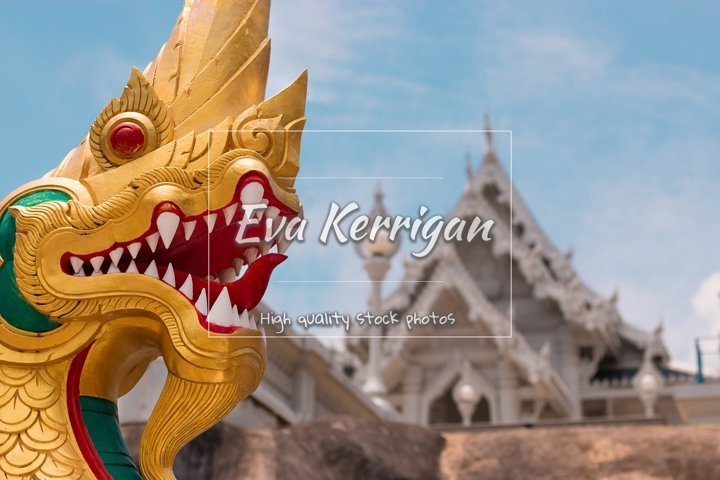 Head of a golden dragon against temple Wat Kaew Korawaram.