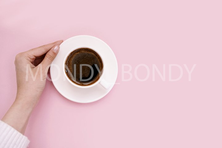 White cup of coffee in hand on a pink background.
