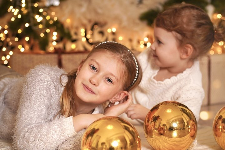 Two girls at Christmas night near christmas tree having fun.