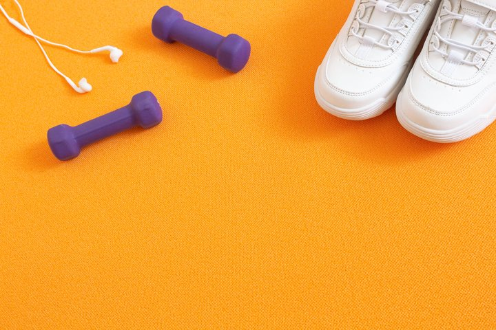 Sneakers, dumbbells and headphones on background