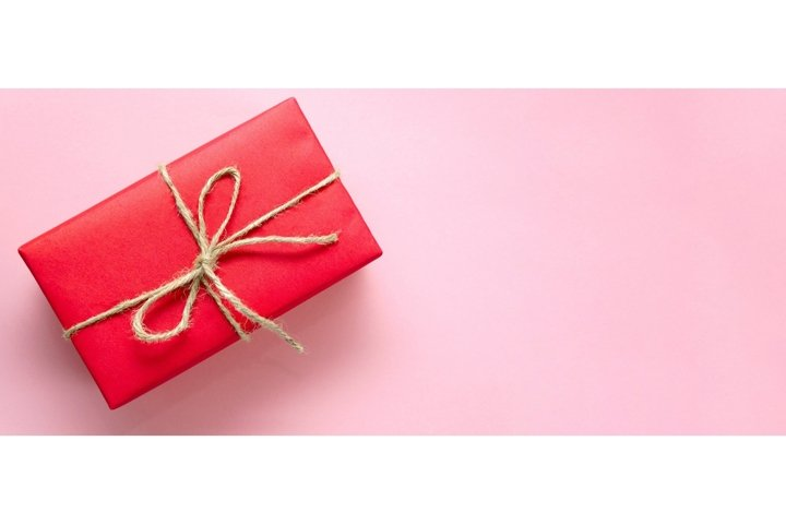 Red gift box tied with twine on pink background. Banner