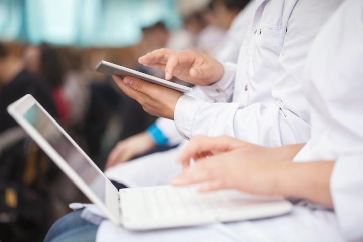 Medical students with pad and laptops in auditorium