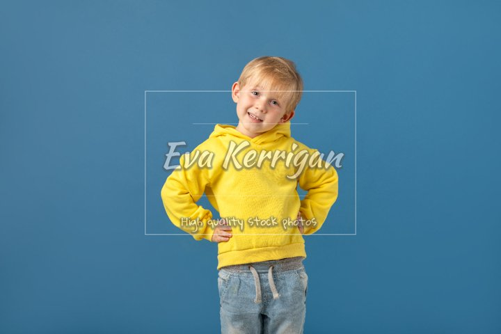 Cheerful child boy in bright yellow glowing sweatshirt.