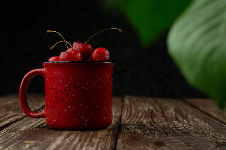 Cherries in a red Cup on a wooden table with space for text