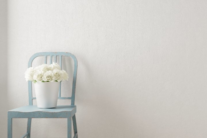 Empty wall background with vintage chair and white roses.