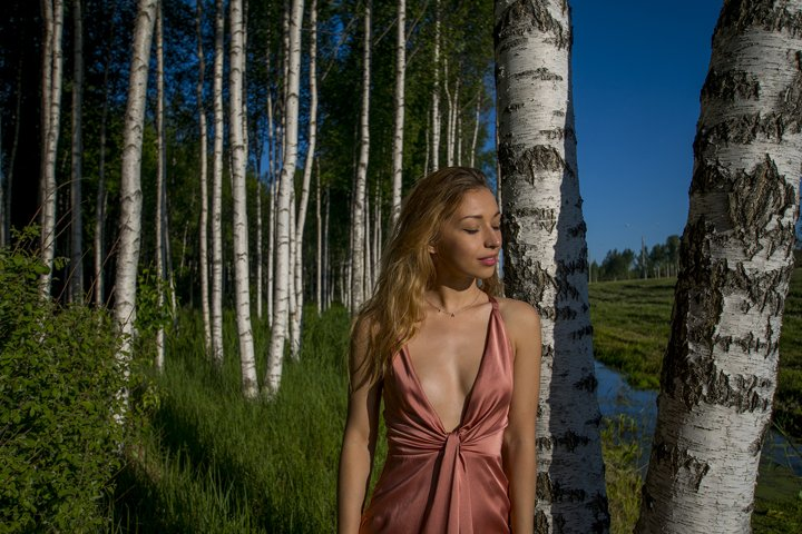 Young slender beautiful girl in a long coral dress