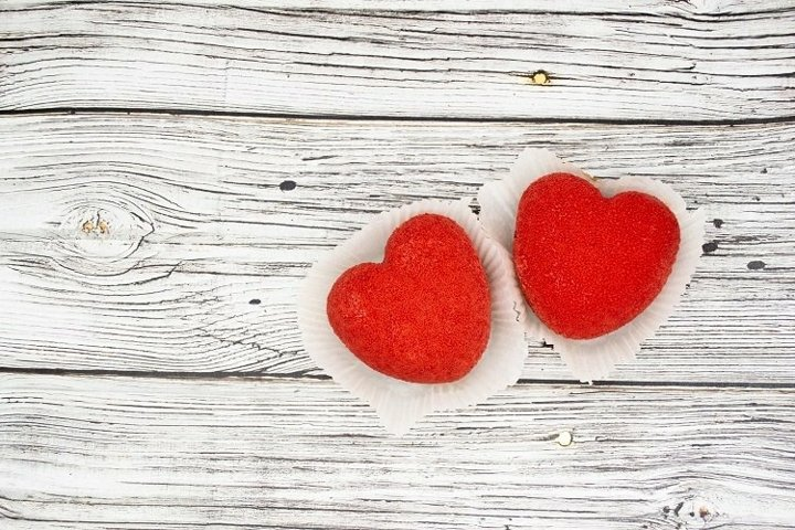 Red heart-shaped cakes on a wooden background