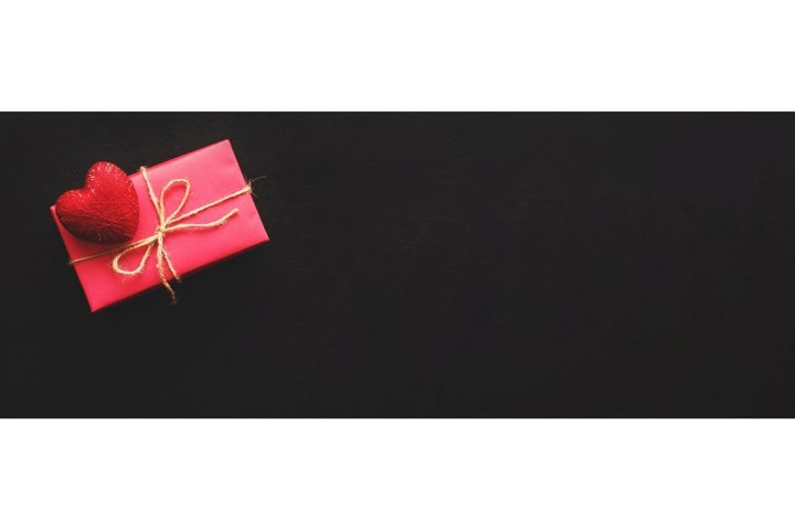 Pink gift box and red heart on black background. Banner