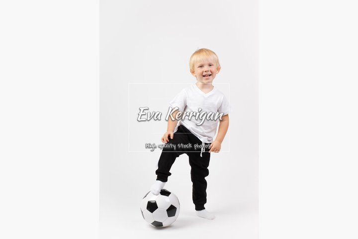 Boy stands with one foot on the ball.