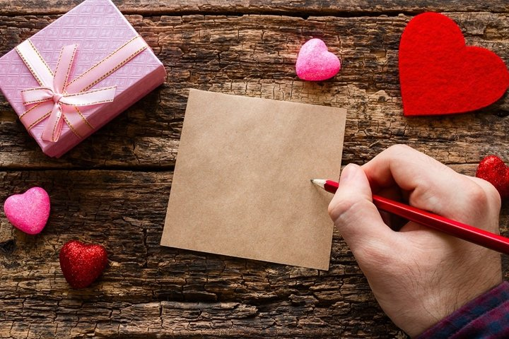 man writes a love note on a wooden background