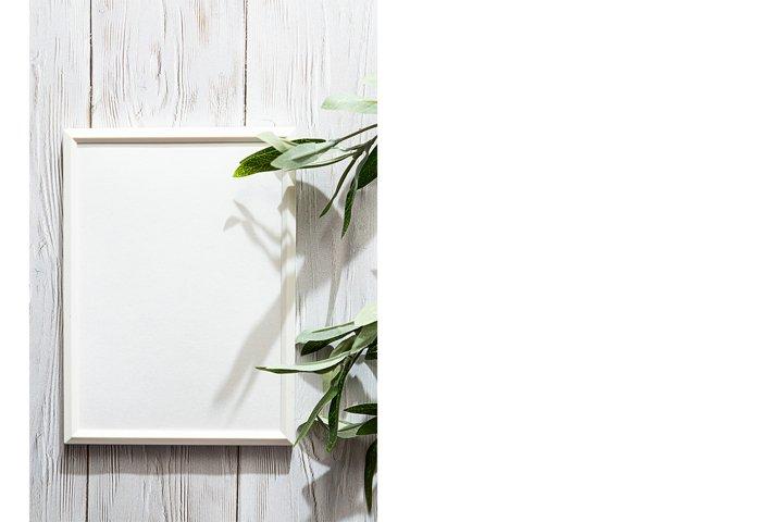 White photo frame with a sprig of eucalyptus on a white
