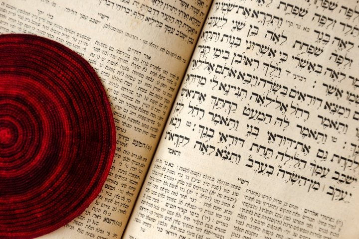 An opened old Jewish Bible and red knitted jewish bale