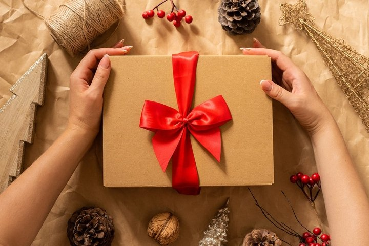 Female hands hold gift box on craft paper background.