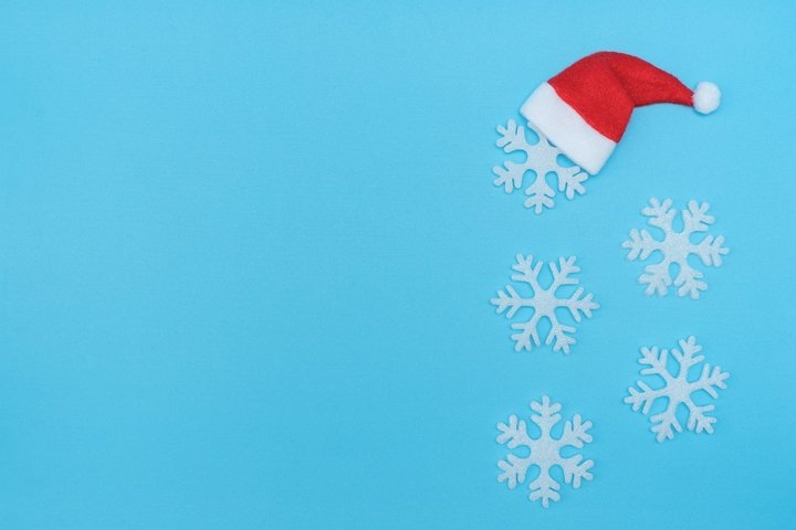 Santa Claus hat and snowflakes on pastel blue background.
