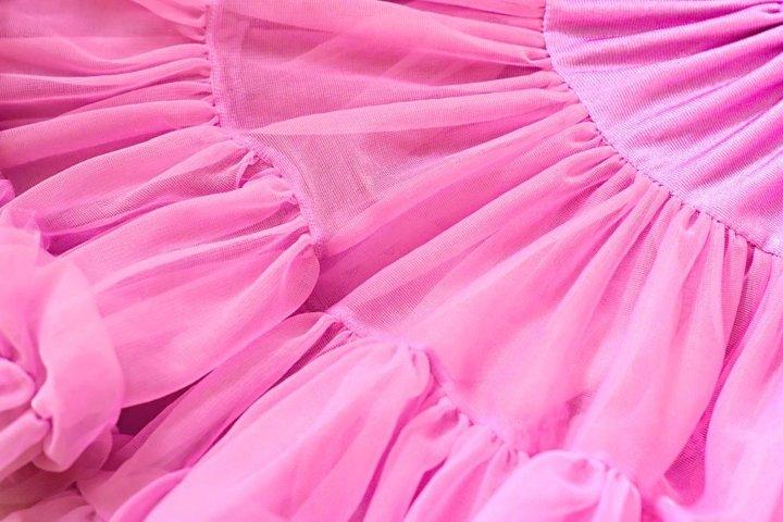 Pink chiffon fabric folds close up. Rose girly dress.