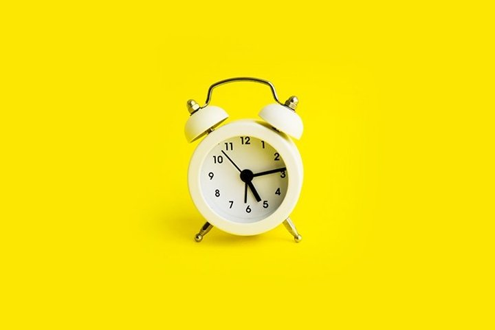 White alarm clock on a yellow background.