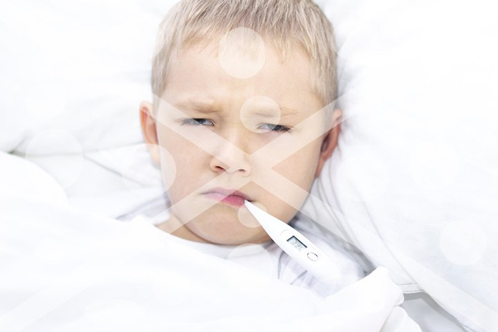 boy lies in bed with a thermometer in his mouth. healthcare
