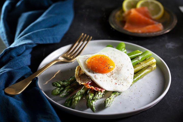 Fried eggs with asparagus, dark moody style