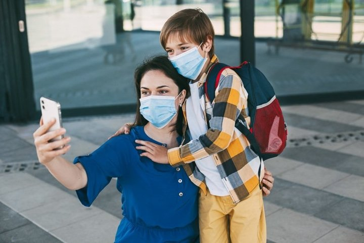 Mom and child with a backpack wearing a mask take a selfie