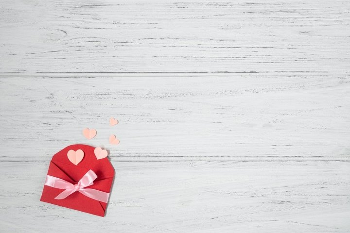 Valentines flat lay with red envelope on white background