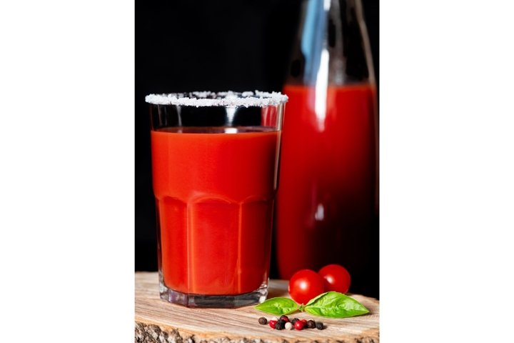 Tomato juice in glass with salty rim on wooden background