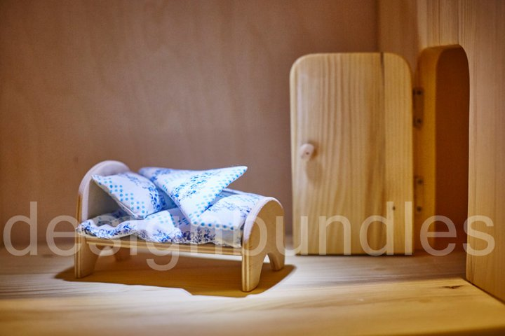 Doll plywood bed with blankets and pillows in the dollhouse.