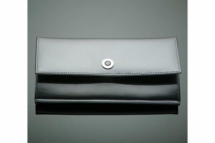 Fashionable designer wallet on a green background