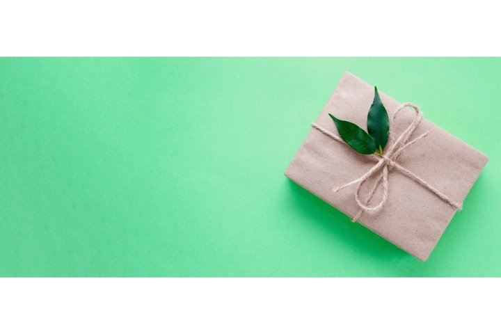 Gift box wrapped in kraft paper decorated with green leaves