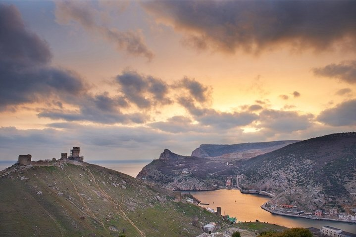 Ancient greek castle on the coast. Sunset above bay
