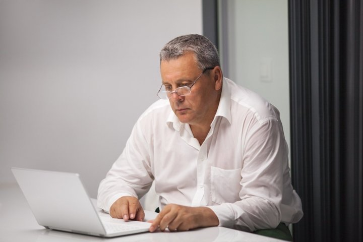 Senior businessman working with laptop in office