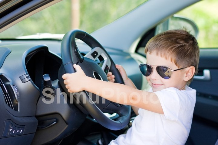 Cute driver. Smilng boy in sunglases in car