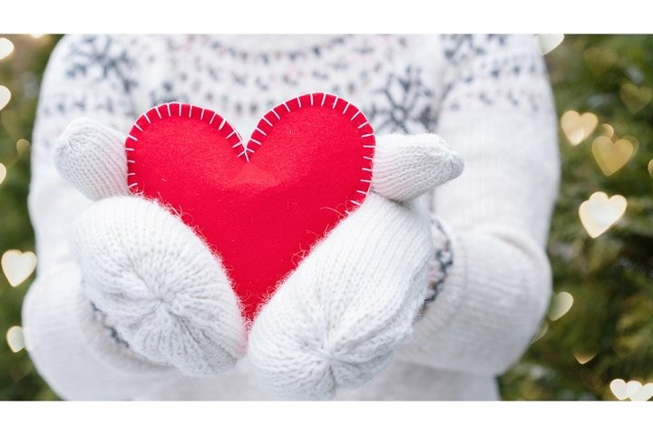 Red heart in hands with knitted mittens for Valentines Day