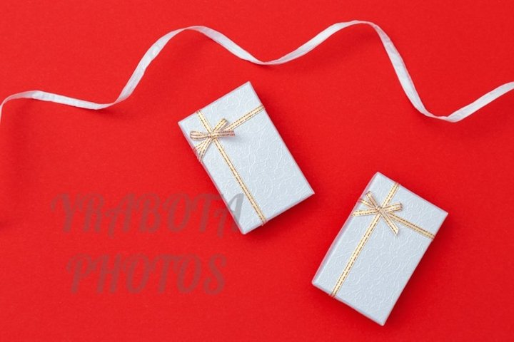 Holiday background with gift boxes on red