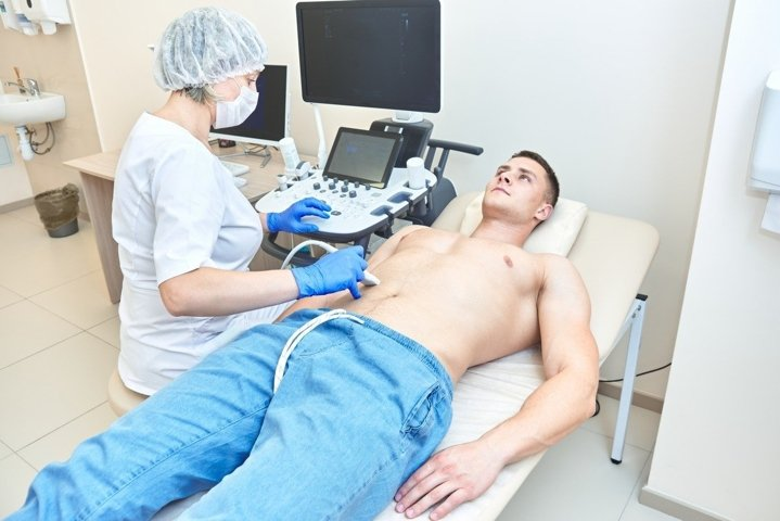 Ultrasound of the abdomen in a man. doctor works