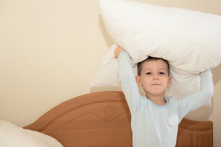 Toddler boy play with pillow on the bed at home.
