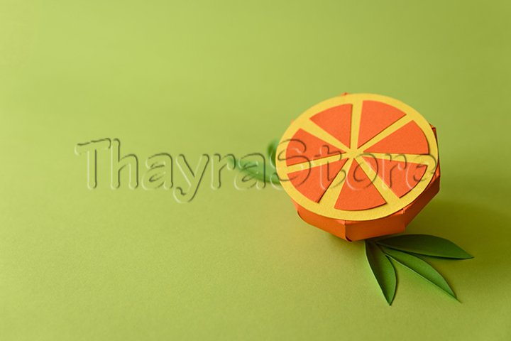 Paper orange fruit on green background.