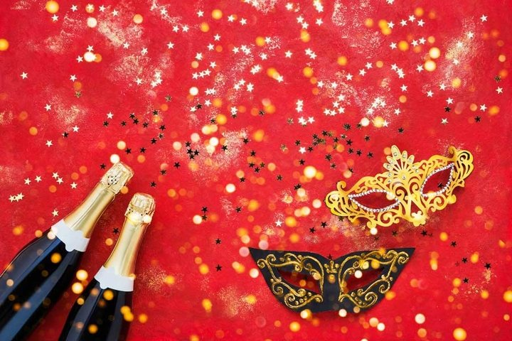Two champagne bottles, carnival mask and golden confetti