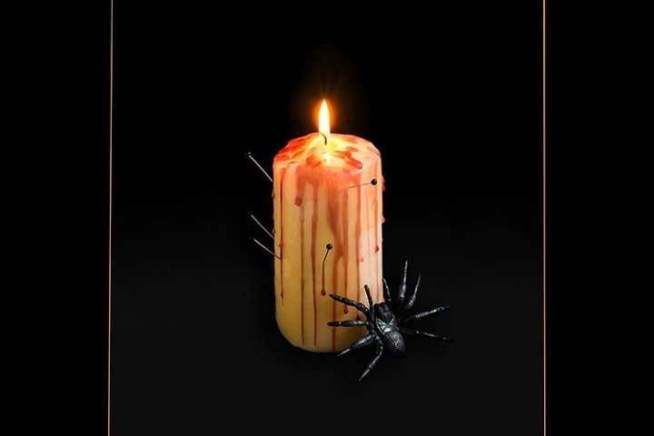 Candle pierced with needles with red drops like blood