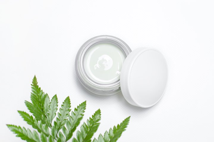Cosmetic cream in container and fresh green leaves on white
