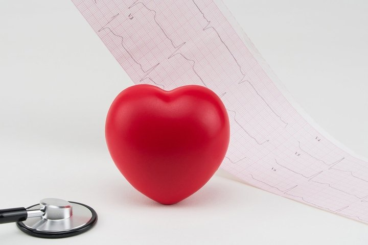 Toy heart and stethoscope on electrocardiogram background