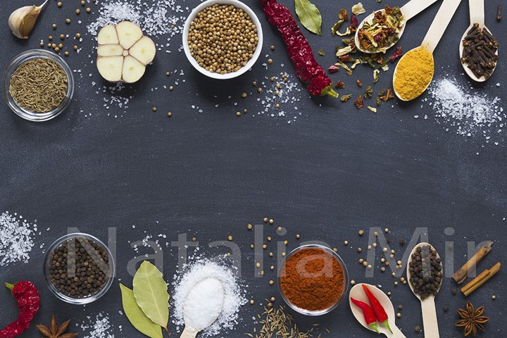 Colourful herbs and spices on dark background.
