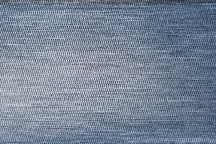 Blue denim background. Texture of shabby soft jeans fabric