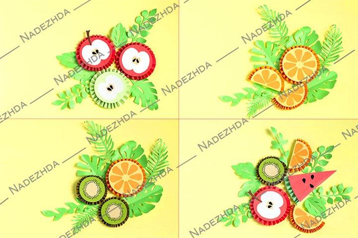 Slices of paper fruits lie on paper leaves