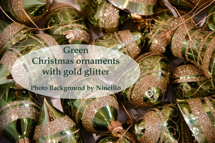 Holiday background of glittered green Christmas ornaments