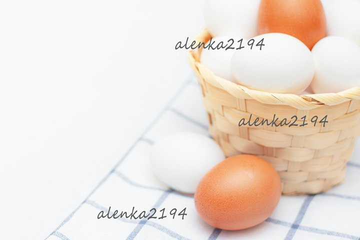 Chicken eggs in a basket on a kitchen towel