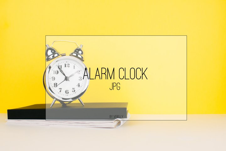 Alarm clock, notebook on white table and yellow background