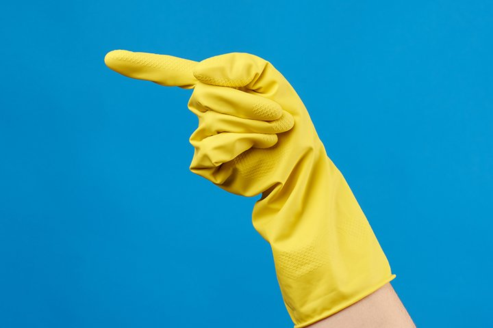 yellow rubber glove for cleaning dressed on a female hand